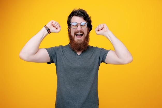 Foto di un vincitore barbuto, bell'uomo urlando e festeggiando con le mani alzate