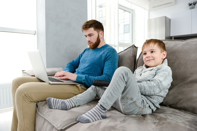 Foto di un giovane padre barbuto vestito con un maglione blu che usa il portatile mentre suo figlio guarda la tv.