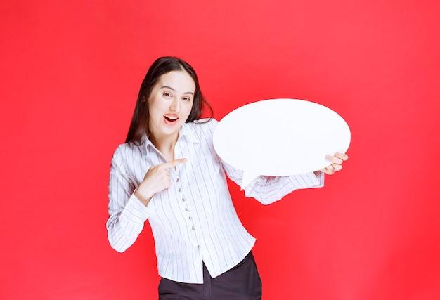 Foto di una bella donna d'affari che indica un fumetto vuoto.