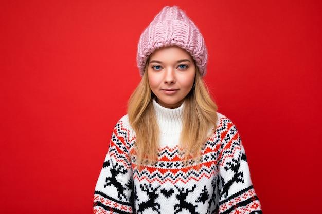 Foto di bella giovane donna bionda seria calma isolata sopra la parete rossa del fondo che indossa winter