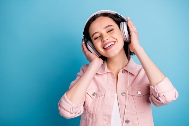 Foto di una bella signora allegra ascolta le cuffie con gli occhi chiusi e goditi la musica