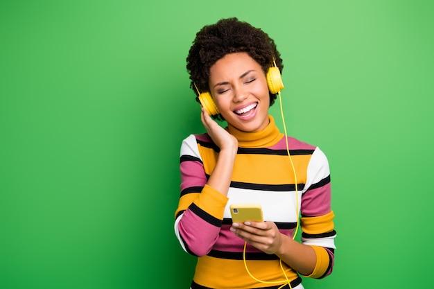 La foto della bella signora della pelle scura del telefono della tenuta della moderna tecnologia auricolari ascolta le nuove canzoni popolari gli occhi chiusi indossano il maglione a strisce casuale