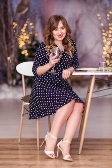 Foto di bella ragazza in un vestito blu si siede a un tavolo