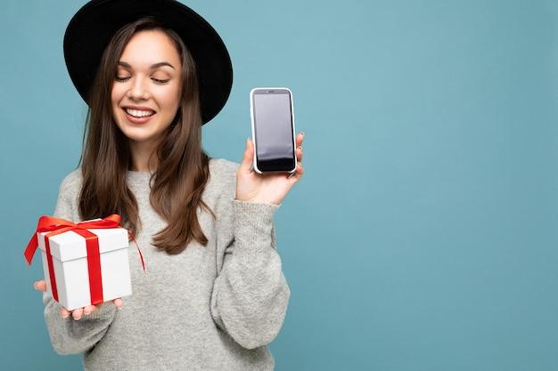 Foto di bella giovane donna castana gioiosa felice isolata sopra la parete blu del fondo che indossa