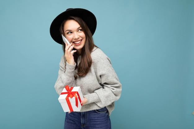 Foto di bella giovane donna castana gioiosa positiva felice isolata sopra la parete blu del fondo