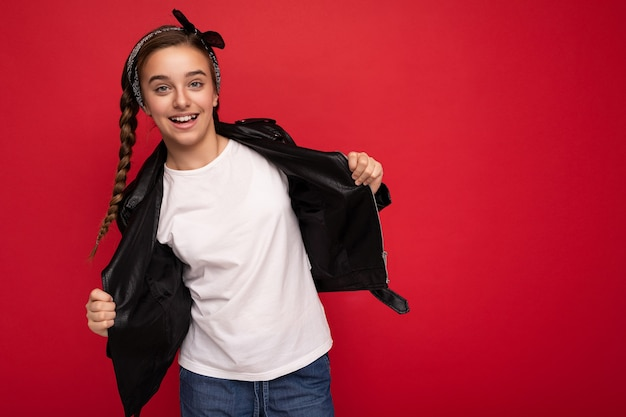 Foto di bella ragazza castana sorridente felice con le trecce che portano la giacca di pelle nera alla moda della bandana e la maglietta bianca