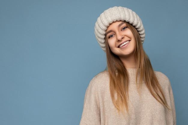 Foto di bella felice sorridente giovane donna bionda scura isolata sopra la parete di fondo blu che indossa un maglione caldo beige e cappello beige lavorato a maglia che guarda l'obbiettivo. spazio libero, copia spazio