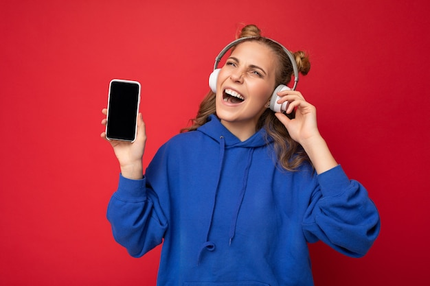 Foto di bella giovane donna sorridente felice che indossa una felpa con cappuccio blu alla moda isolata sopra il rosso