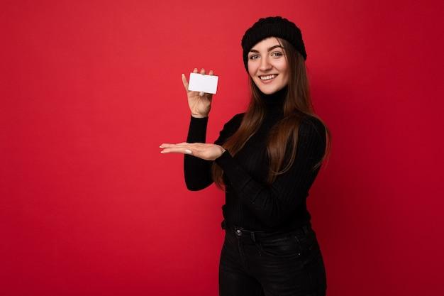 Foto di bella giovane donna castana felice che porta maglione nero e cappello isolato sulla tenuta rossa della parete e che mostra la carta di credito.
