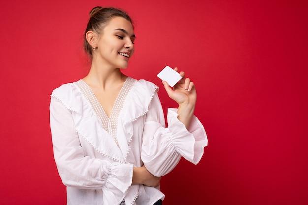 Foto di bella giovane donna bionda scura felice che indossa camicetta bianca isolata sopra la carta di credito della tenuta della parete rossa che esamina la carta di plastica. spazio vuoto