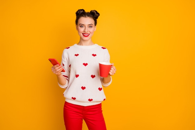 La foto del telefono di navigazione della bevanda del caffè caldo della tenuta della bella signora gode del maglione bianco del modello dei cuori di usura del tempo libero
