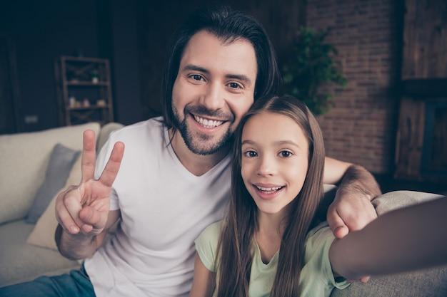 La foto della bella bambina adorabile e del bel giovane papà si siede sul comodo divano