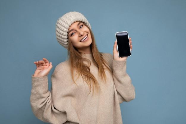 Foto di bella giovane donna di bell'aspetto positiva che indossa un maglione beige alla moda e maglia beige