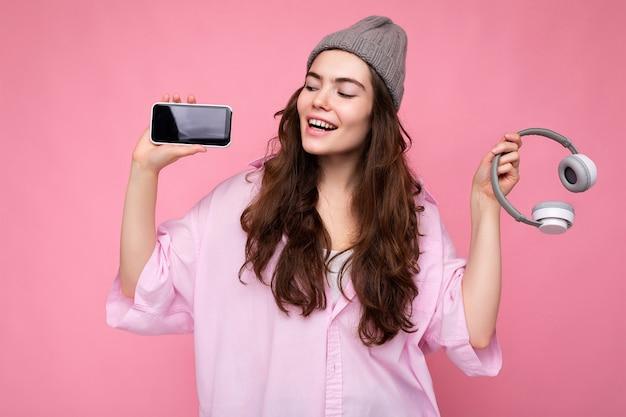 Foto di una bella giovane donna sorridente positiva che indossa un abito casual elegante isolato su colorato