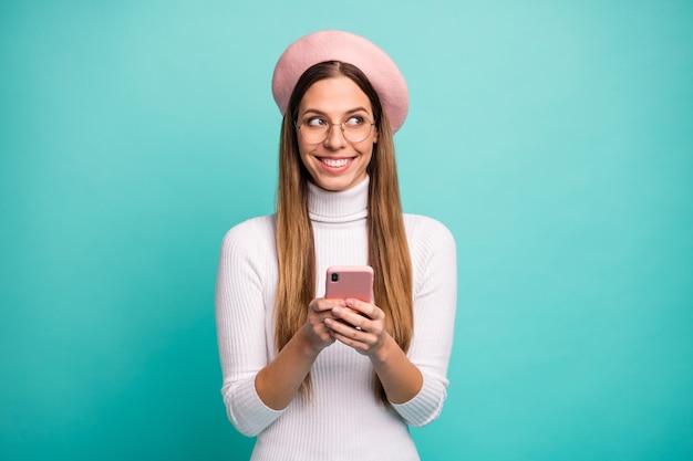 Foto di bella bella signora tenere le mani del telefono guardare lato spazio vuoto vedere vendita annuncio banner indossare specifiche moderno berretto rosa berretto dolcevita bianco isolato colore verde acqua sfondo