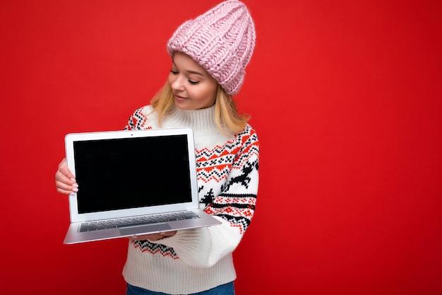 Foto di una bella giovane donna bionda sorridente che tiene in mano un computer portatile con uno schermo monitor vuoto con