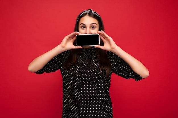Foto di una bella ragazza adolescente sorridente di bell'aspetto che indossa abiti casual ed eleganti in piedi isolata su