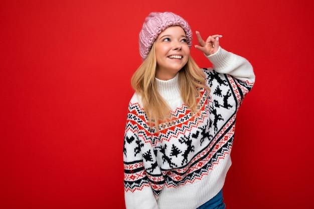 Foto di bella giovane donna bionda sorridente che porta cappello lavorato a maglia caldo e maglione caldo di inverno