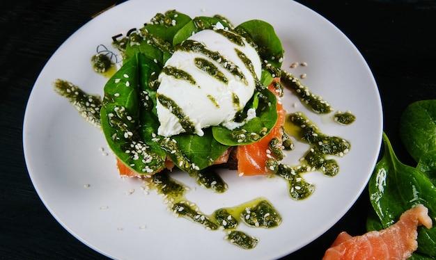 Foto del bellissimo e gustoso piatto con uovo in camicia e salmone con insalata