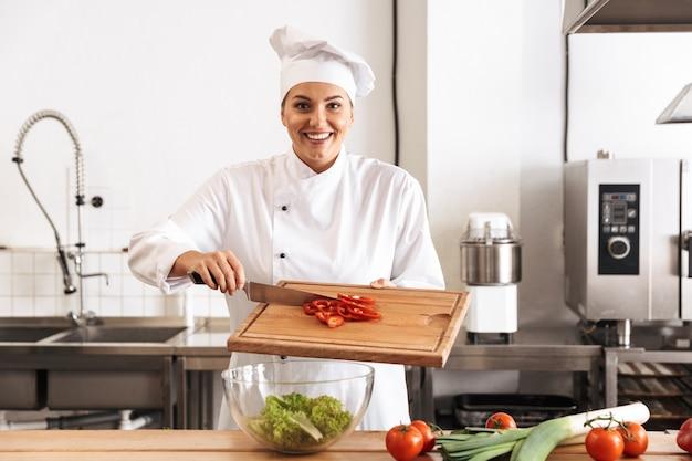 Foto del cuoco unico della bella donna che indossa l'uniforme bianca che fa insalata con le verdure fresche, in cucina al ristorante