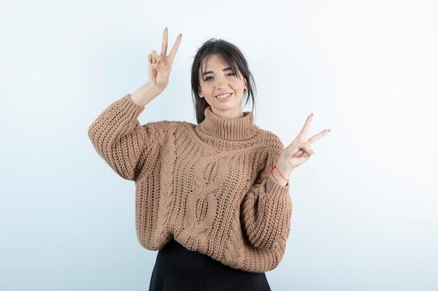 Foto di bella donna in maglione lavorato a maglia in piedi su sfondo bianco.