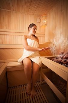 Foto di una bella donna seduta accanto al forno nella sauna