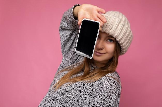 Foto di bella giovane donna bionda che indossa un maglione grigio casual e cappello beige isolato sopra il muro rosa tenendo in mano e mostrando il telefono cellulare con display vuoto.