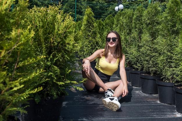 Foto di bella ragazza in posa tra i fiori in una serra. stile di vita