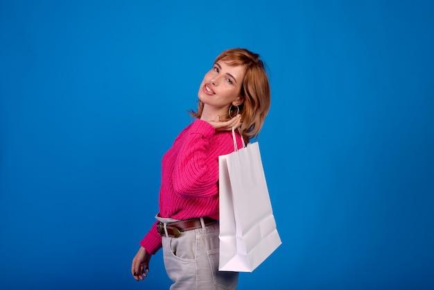 Foto di una bella ragazza giovane rossa in un maglione rosa con pacchetti in vendita.