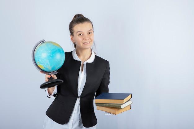 Foto di bella giovane insegnante con libri e globo in piedi su bianco.