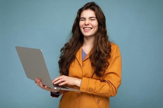Foto di bella giovane donna che tiene il computer portatile del computer isolato sopra la parete variopinta.