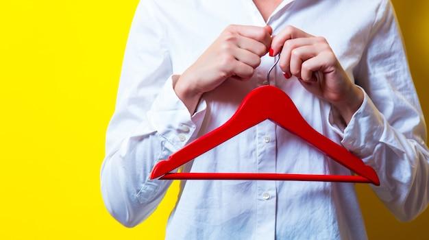 Foto di bella giovane donna con appendiabiti rosso sul giallo