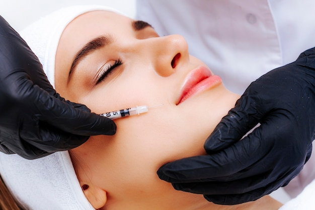 Foto biorivitalizzazione del viso in una clinica professionale di cosmetologia. iniezioni antietà.