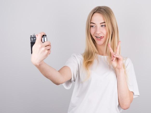 Foto della ragazza bionda in maglietta casual che mostra il segno di pace e prendendo selfie con la vecchia macchina fotografica