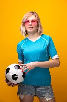 Foto di bionda in occhiali rosa con pallone da calcio su sfondo arancionein studio