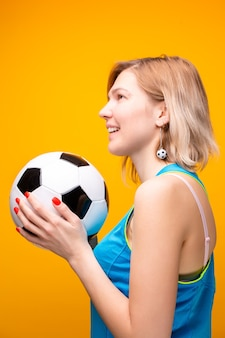 Foto di bionda con pallone da calcio su sfondo giallo in studio