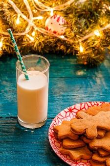 Foto del tavolo blu con biscotti di natale, bicchiere di latte, rami di abete rosso con ghirlanda in fiamme