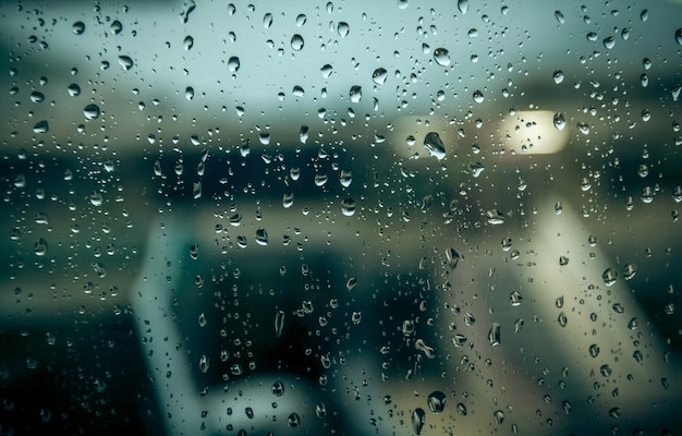 Foto di un edificio sfocato attraverso la finestra con gocce di pioggia