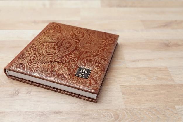 Fotolibro, quaderno o diario con copertina in vera pelle. colore marrone con stampa decorativa. album di foto di famiglia. copia spazio.