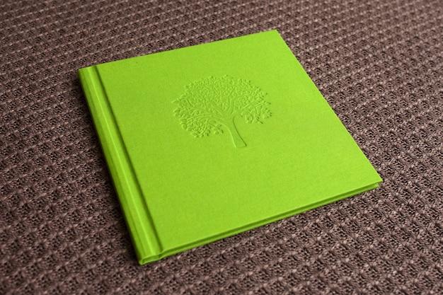 Fotolibro con copertina in tessuto. colore verde chiaro con stampigliatura decorativa.