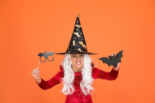 Oggetti di scena per cabine fotografiche. piccola ragazza con cappello da strega nero. vacanza autunnale. unisciti alla celebrazione. piccolo bambino in costume da strega. incantesimo magico. piccola strega dai capelli bianchi. mago o mago. festa di halloween.