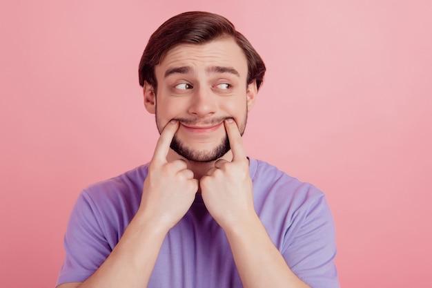 La foto di un uomo annoiato e infelice sembra uno spazio vuoto le dita toccano le labbra pensano che il sogno sia isolato su uno sfondo di colore rosa
