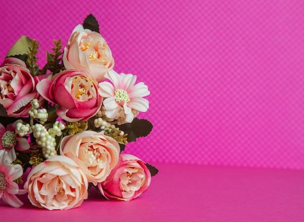 Foto di un mazzo di fiori regalo beige sotto forma di una scatola su uno sfondo rosa vista frontale in alto