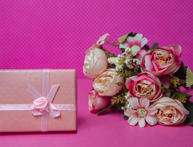 Foto di un mazzo di fiori regalo rosa sotto forma di una scatola su uno sfondo rosa vista frontale in alto