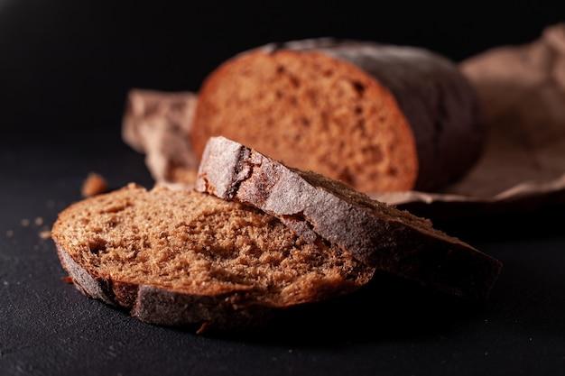 Foto di pane su una borsa artigianale la confezione giace su una superficie di cemento scuro