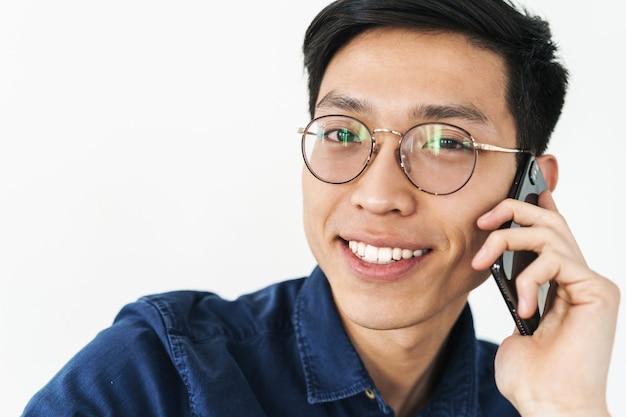 Foto di un uomo d'affari asiatico bruna che indossa occhiali seduto su una sedia e parla su smartphone mentre lavora in ufficio isolato su un muro bianco