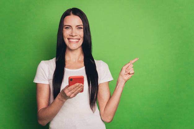 Foto di una signora bruna con il telefono che dirige il dito spazio vuoto isolato sfondo verde
