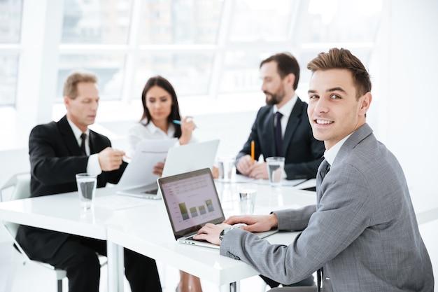 Foto di un uomo d'affari seduto al tavolo con un laptop in sala conferenze con i colleghi e che guarda la telecamera