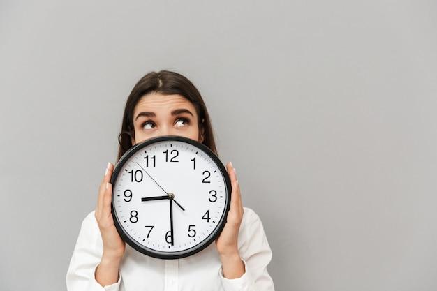 Foto di donna d'affari in camicia bianca guardando verso l'alto mentre copre il viso con un grande orologio rotondo, isolato sopra il muro grigio