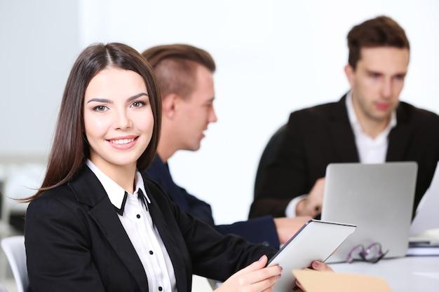 Foto di donna d'affari con il suo staff nella sala conferenze durante la riunione